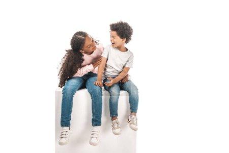 Foto de Linda hermana africaica americana mirando a un hermano adorable mientras se sienta en un cubo blanco juntos aislado en blanco. - Imagen libre de derechos