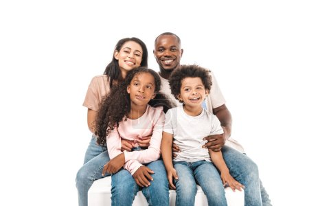 Photo pour Happy african american wife and husband hugging adorable children while sitting isolated on white - image libre de droit