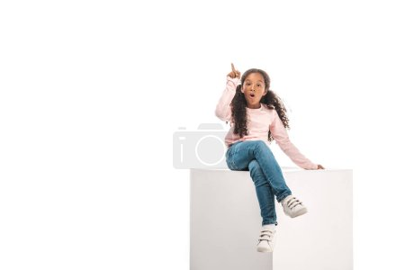 Photo for Excited african american kid showing idea sign while sitting isolated on white - Royalty Free Image