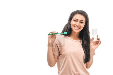 Photo pour Femme afro-américaine souriante tenant brosse à dents et dentifrice tout en regardant la caméra isolée sur blanc - image libre de droit