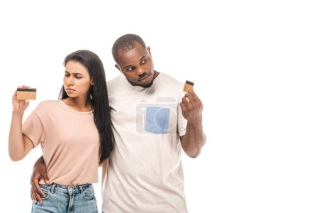 Photo for Skeptical african american couple looking at credit cards isolated on white - Royalty Free Image