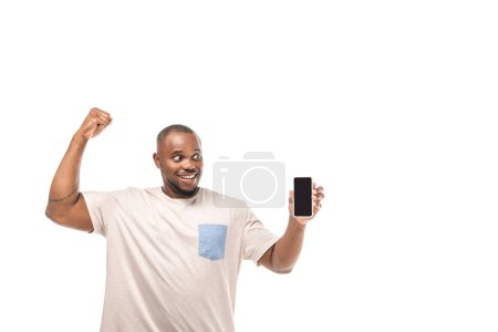 Photo for Cheerful african american man holding smartphone with blank screen and showing winner gesture isolated on white - Royalty Free Image