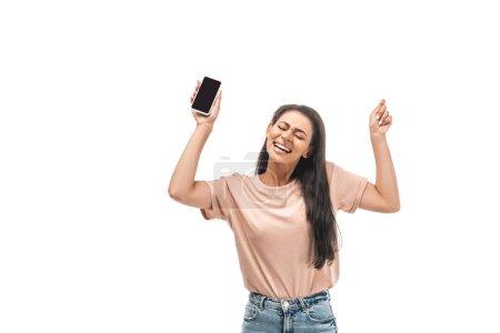 Photo pour Excitée femme afro-américaine tenant smartphone avec écran blanc et montrant geste gagnant isolé sur blanc - image libre de droit