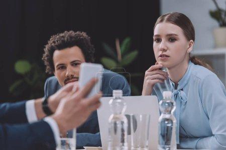 Photo pour Crochet vue d'un homme d'affaires montrant un smartphone à des collègues multiculturels - image libre de droit