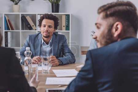 young african american businessman sitting in meeting room near multicultural colleagues