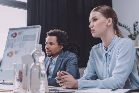 Photo pour Homme et femme d'affaires multiculturel attentif assis à son bureau lors d'une réunion d'affaires - image libre de droit