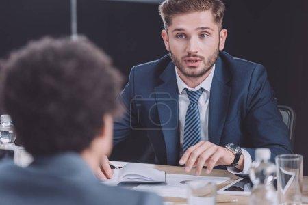 Photo pour Focalisation sélective du jeune homme d'affaires parlant lors d'une réunion d'affaires - image libre de droit