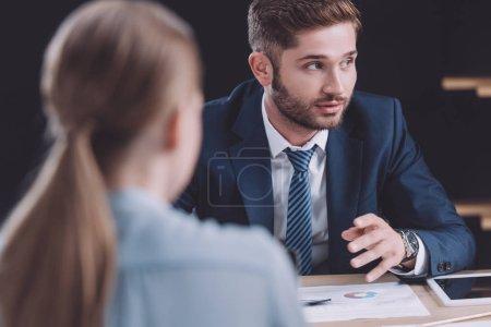Photo pour Foyer sélectif de bel homme d'affaires parlant à la réunion d'affaires - image libre de droit