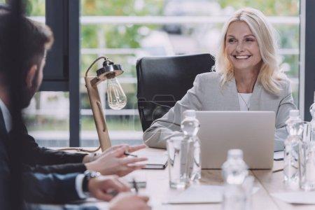 Photo pour Une femme d'affaires attrayante sourit lors d'une rencontre d'affaires avec de jeunes collègues - image libre de droit