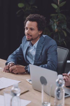 Photo for Attentive african american businessman sitting near laptop at business meeting - Royalty Free Image