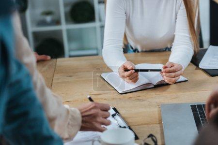 Photo pour Vue en coupe de femmes d'affaires tenant des stylos près d'un cahier et d'un tableau à reliure lors d'une réunion d'affaires - image libre de droit