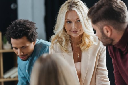 Photo for Selective focus of attractive businesswoman looking at colleague at business meeting with multicultural coworkers - Royalty Free Image