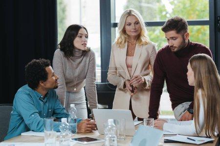 attraktive, reife Geschäftsfrau schaut Kollegin bei Geschäftstreffen mit multikulturellen Mitarbeitern an