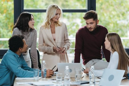 young multicultural businesspeople talking to mature businesswoman at business meeting