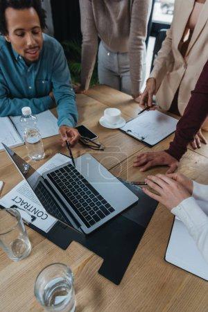 Photo pour Vue recadrée de gens d'affaires debout près d'un homme d'affaires afro-américain pointant vers un ordinateur portable - image libre de droit