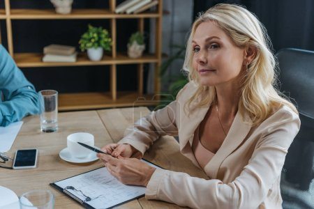 attractive, mature businesswoman sitting at desk in meeting room