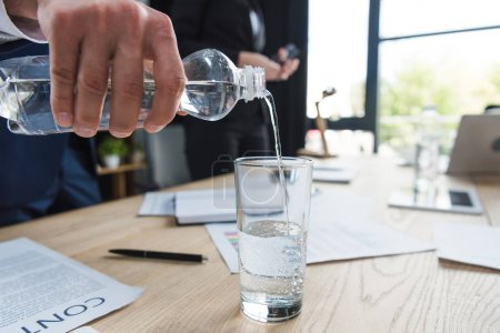 Photo for Cropped view of businessman pouring water in glass - Royalty Free Image