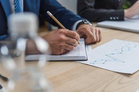 Photo pour A vu un homme d'affaires écrire dans un carnet pendant une réunion d'affaires - image libre de droit
