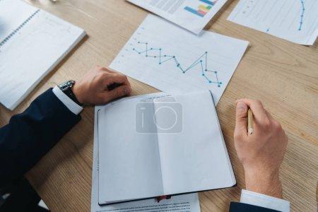 Photo pour Crochet vue d'un homme d'affaires assis près d'un carnet vierge et de papiers avec infographie - image libre de droit