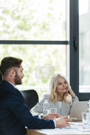 positive, aufmerksame Geschäftsfrau hört jungen Kollegen bei Geschäftstreffen zu