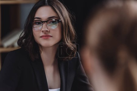 Photo for Selective focus of pretty businessman in glasses looking at colleague at business meeting - Royalty Free Image