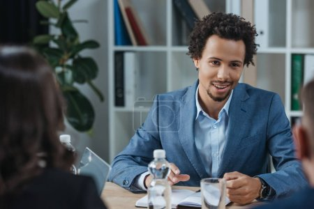 selective focus of positive african american businessman looking at colleagues at business meeting