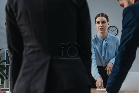 Photo for Selective focus of young businesswoman looking at colleagues in meeting room - Royalty Free Image