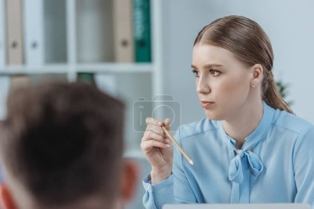 selective focus of attentive businesswoman listening to colleagues and holding pencil at business meeting