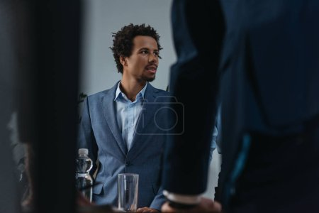 Photo for Selective focus of african american businessman looking away during business meeting - Royalty Free Image
