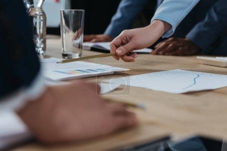 Photo pour Crochet vue d'une femme d'affaires pointant du doigt lors d'une réunion d'affaires avec des collègues - image libre de droit