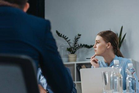 Photo pour Une femme d'affaires attentive écoutant ses collègues au cours d'une réunion d'affaires - image libre de droit