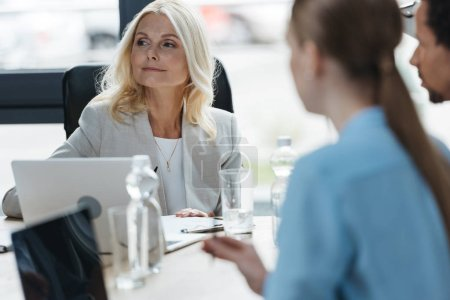 Photo for Selective focus of confident businesswoman at business meeting with young multicultural colleagues - Royalty Free Image