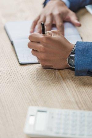 Photo pour Crochet vue d'un homme d'affaires écrivant dans un cahier sur un bureau en bois - image libre de droit