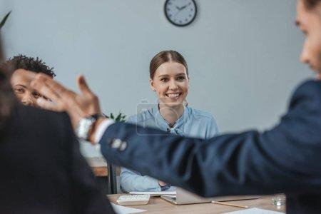 Photo pour Foyer sélectif de sourire femme d'affaires regardant collègue pointant avec la main près de collègues multiculturels - image libre de droit