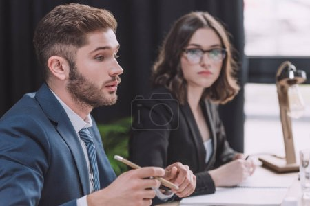selective focus of young businessman talking at business meeting while sitting near attentive businesswoman
