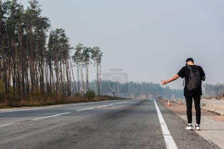 Photo for Back view of man with backpack gesturing while hitchhiking on empty road near green trees - Royalty Free Image