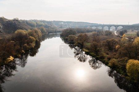 Photo pour Eau dans la rivière près des arbres dans la forêt verte près du pont - image libre de droit