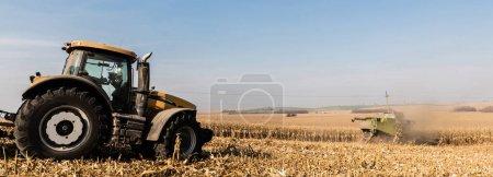 Photo pour Plan panoramique de tracteurs sur champ doré contre ciel bleu - image libre de droit