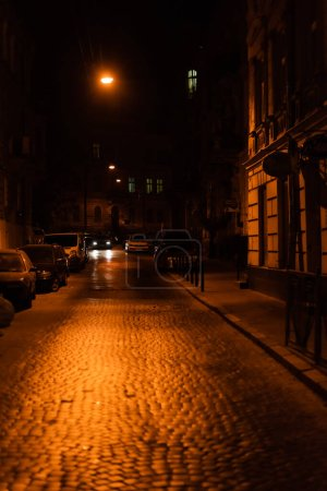 Photo for LVIV, UKRAINE - OCTOBER 23, 2019: cars parked near road and building at night - Royalty Free Image