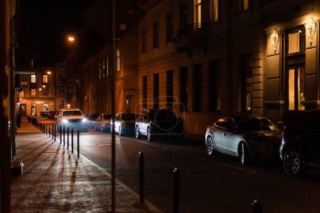 Photo pour LVIV, UKRAINE - 23 OCTOBRE 2019 : éclairage de la voiture dans la rue près des bâtiments avec lettrage cyrillique la nuit - image libre de droit