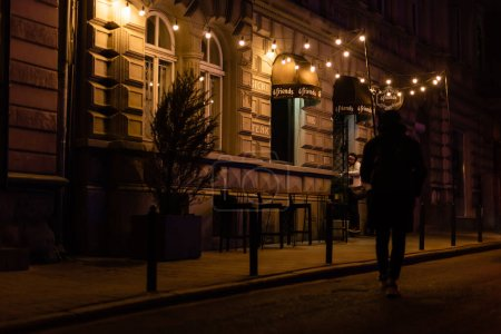Photo for LVIV, UKRAINE - OCTOBER 23, 2019: man walking on street near building with light bulbs - Royalty Free Image