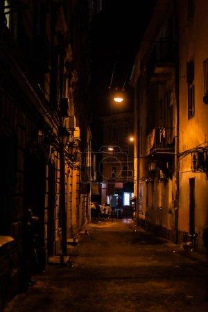 Photo pour Personnes marchant dans la rue sombre avec de vieilles maisons - image libre de droit