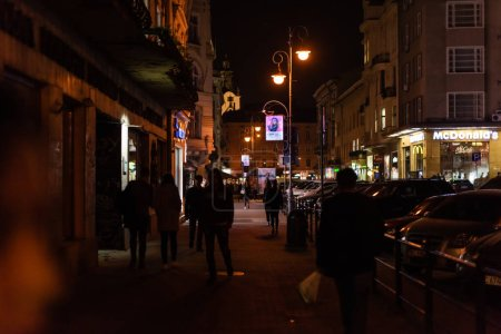 LVIV, UKRAINE - OCTOBER 23, 2019: people walking on dark street near mcdonalds building