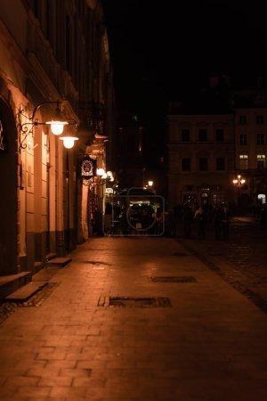 LVIV, UKRAINE - OCTOBER 23, 2019: street lamps with lighting near 39 hotel lettering near building