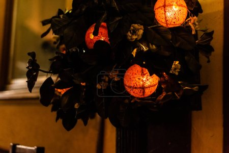Photo for Selective focus of decorative balls with lighting near green leaves - Royalty Free Image