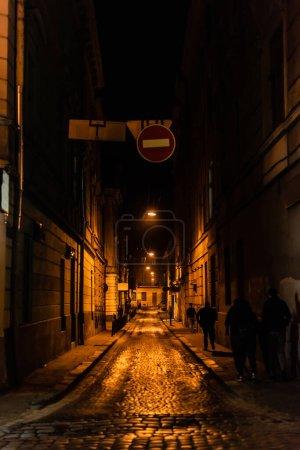 Photo pour LVIV, UKRAINE - 23 OCTOBRE 2019 : silhouette de personnes marchant dans la rue sombre à lviv - image libre de droit