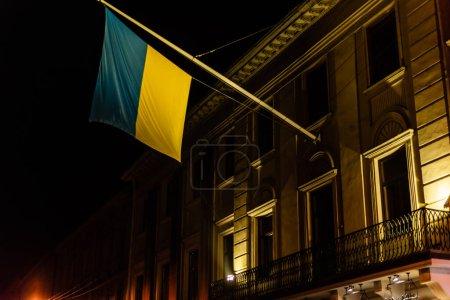 Photo pour Vue à angle bas du drapeau ukrainien près de l'ancien bâtiment à lviv - image libre de droit