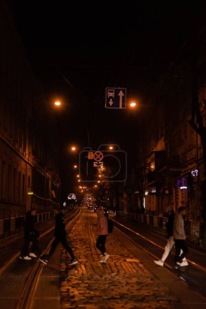 LVIV, UKRAINE - OCTOBER 23, 2019: silhouette of people crossing road near cars in evening