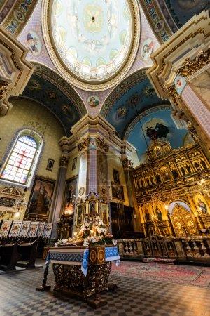 Foto de LVIV, UCRANIA - 23 DE OCTUBRE DE 2019: vista de bajo ángulo interior de la iglesia de carmelita con altar dorado y hermosas pinturas - Imagen libre de derechos