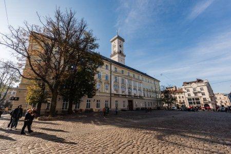 Photo pour LVIV, UKRAINE - 23 OCTOBRE 2019 : façade de la tour de l'hôtel de ville de Lviv et les gens marchant le long de la rue - image libre de droit